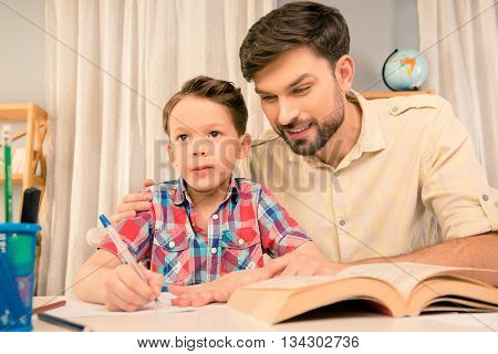 Young Father Teaching Little Son How To Write