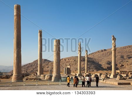 SHIRAZ IRAN - SEPTEMBER 17 2014: Group of tourists visiting ruins of Apadana Palace in Persepolis city. construction of this city began at 518 BC under rule of King Darius from Achaemenid dynasty.
