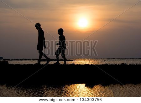 Group Of Child Walking At Sunset On The Beach