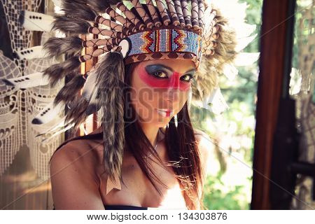Beautiful young woman wearing an Indian headdress
