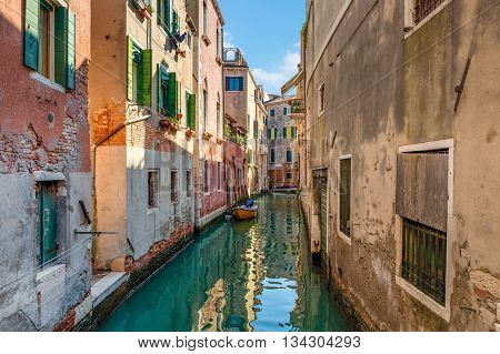 Narrow canal among old houses in Venice, Italy.