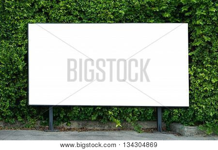 Empty billboard White billboard on spring summer green leaves background Blank billboard mockup template for advertisement present