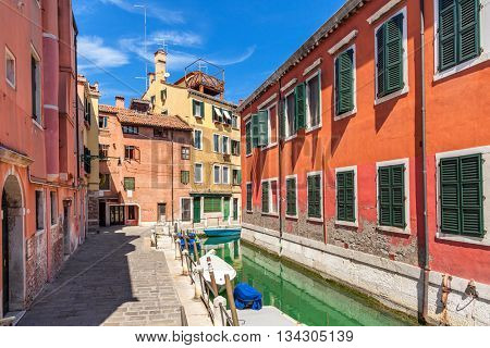 Narrow street and oats on canal between colorful houses under blue sky in Venice, Italy.