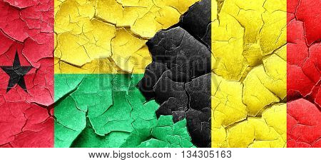 Guinea bissau flag with Belgium flag on a grunge cracked wall