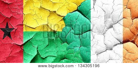 Guinea bissau flag with Ireland flag on a grunge cracked wall