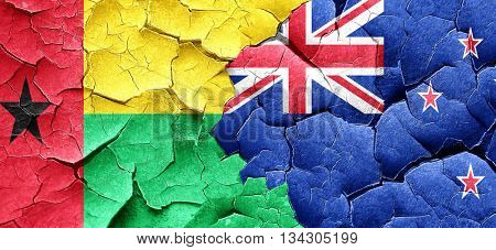 Guinea bissau flag with New Zealand flag on a grunge cracked wal