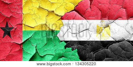 Guinea bissau flag with egypt flag on a grunge cracked wall