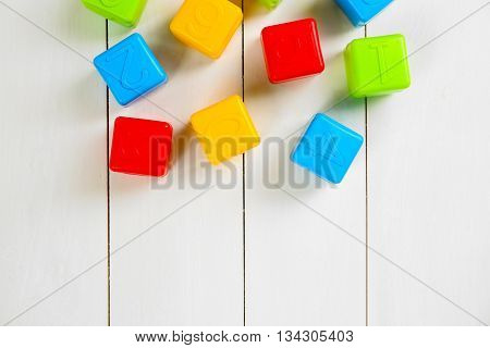 Colorful children's cubes on white wooden background