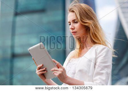 Beautiful woman using electronic tab in the street