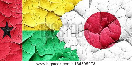 Guinea bissau flag with Japan flag on a grunge cracked wall