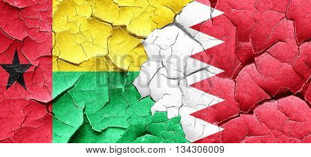 Guinea bissau flag with Bahrain flag on a grunge cracked wall