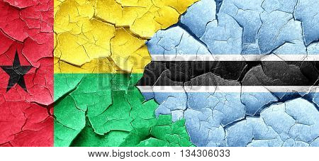 Guinea bissau flag with Botswana flag on a grunge cracked wall