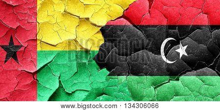 Guinea bissau flag with Libya flag on a grunge cracked wall