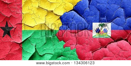Guinea bissau flag with Haiti flag on a grunge cracked wall