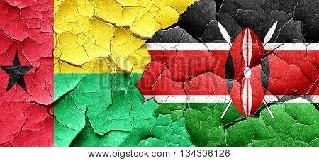 Guinea bissau flag with Kenya flag on a grunge cracked wall