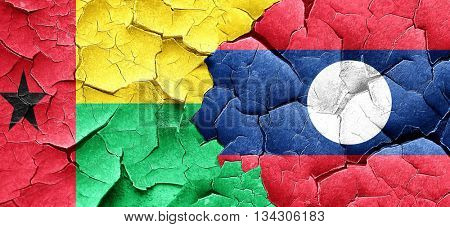 Guinea bissau flag with Laos flag on a grunge cracked wall
