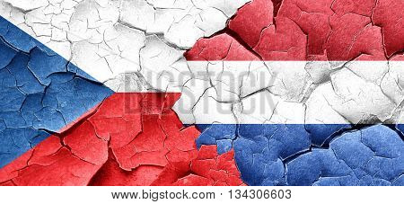 czechoslovakia flag with Netherlands flag on a grunge cracked wa