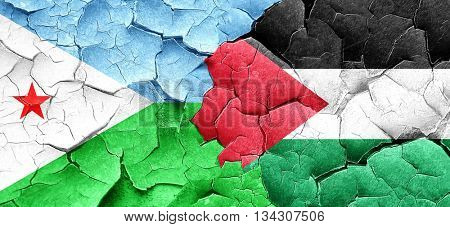 Djibouti flag with Palestine flag on a grunge cracked wall