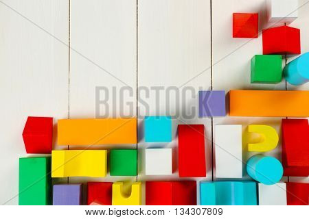 Colorful wooden children's building blocks on white wooden background