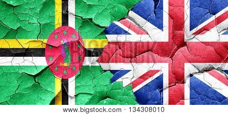 Dominica flag with Great Britain flag on a grunge cracked wall