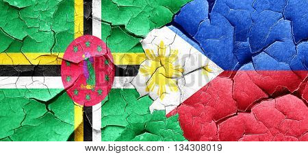 Dominica flag with Philippines flag on a grunge cracked wall