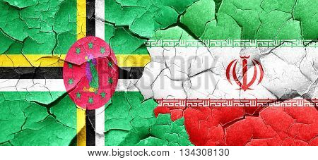 Dominica flag with Iran flag on a grunge cracked wall