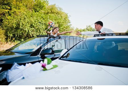 wedding couple at car sunroof at wedding