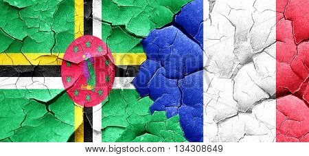 Dominica flag with France flag on a grunge cracked wall