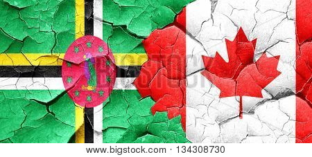 Dominica flag with Canada flag on a grunge cracked wall