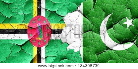 Dominica flag with Pakistan flag on a grunge cracked wall