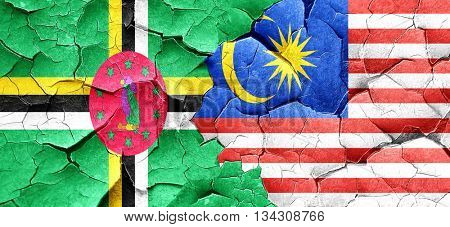 Dominica flag with Malaysia flag on a grunge cracked wall