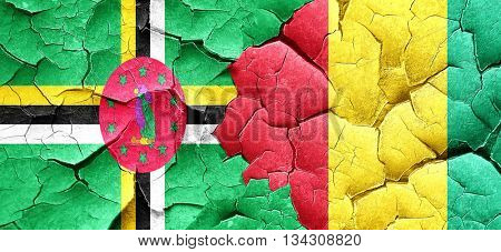 Dominica flag with Guinea flag on a grunge cracked wall