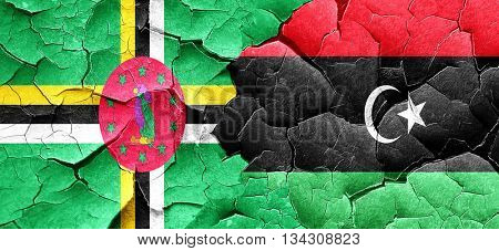 Dominica flag with Libya flag on a grunge cracked wall