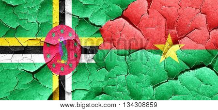 Dominica flag with Burkina Faso flag on a grunge cracked wall