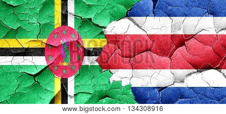 Dominica flag with Costa Rica flag on a grunge cracked wall