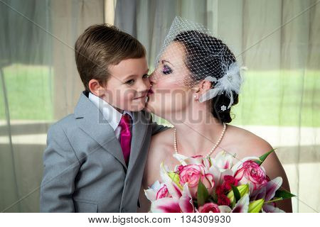 A young bride kisses her son on her wedding day in her pre-wedding portrait. She holds her bouquet and he leans in for a kiss.