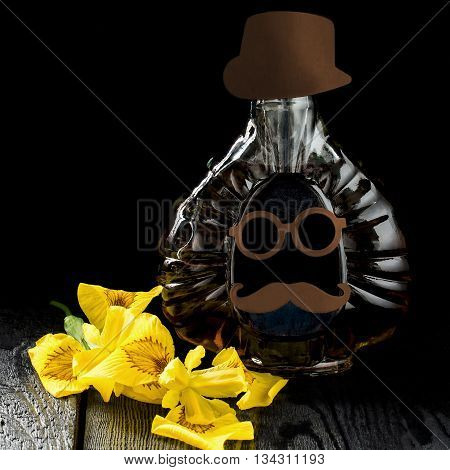 Fathers Day composition. Bottle with homemade fun applique in the shape of the face iris flowers on dark wooden background with space for text. Square image selective focus