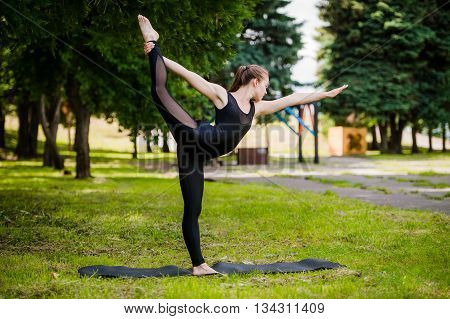 Young girl practicing yoga in nature in the woods on a background of green trees and grass. She balances on one leg