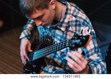 Musician tuning strings on his bass-guitar. Front view on bass player spinning guitar tuners. Closeup on young guy with bass guitar