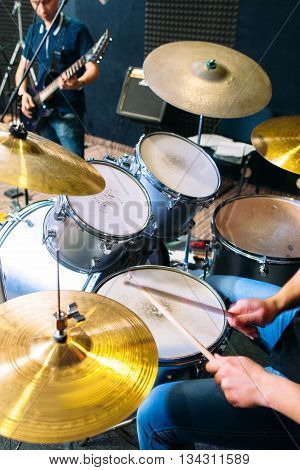 Unrecognizable drummer plays on drum set alive close-up. Front view on modern drum set and playing on it alive drummers hands. Scene background