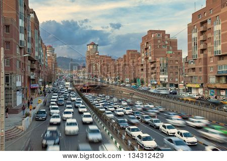 TEHRAN IRAN - FEBRUARY 19 2016: Cars Passing Through Tohid Tunnel with Milad Tower and Alborz Mountains in Background. Tohid Tunnel is the third longest urban tunnel in Middle East.