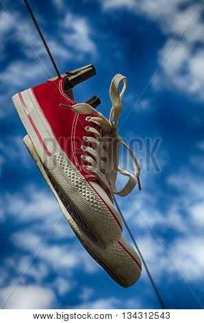 pair of red sneakers on a clothesline on a blue sky background