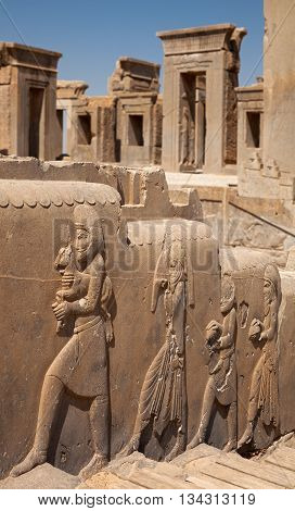 Stone frames of doorways to the palace of Darius behind embossed bas relief carvings of servants bringing gifts to the Achaemenian King at Persepolis of Shiraz.