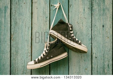Dark blue sneakers hang on a nail on a blue wooden wall canvas shoetoning