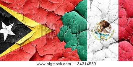 east timor flag with Mexico flag on a grunge cracked wall