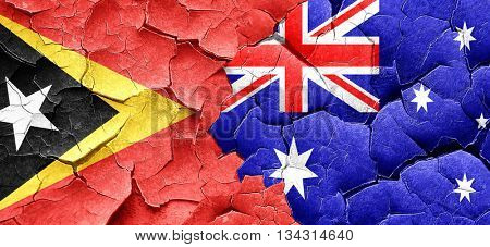 east timor flag with Australia flag on a grunge cracked wall