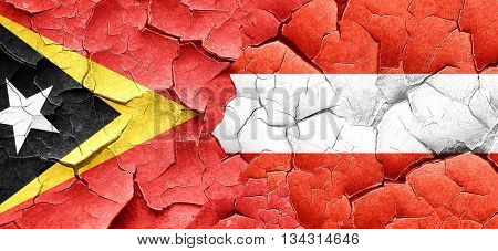 east timor flag with Austria flag on a grunge cracked wall