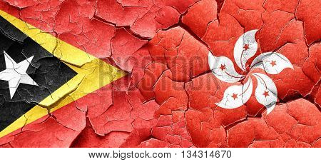 east timor flag with Hong Kong flag on a grunge cracked wall