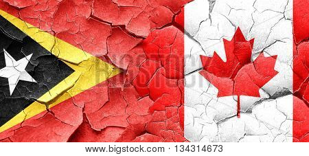 east timor flag with Canada flag on a grunge cracked wall