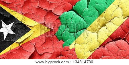 east timor flag with congo flag on a grunge cracked wall